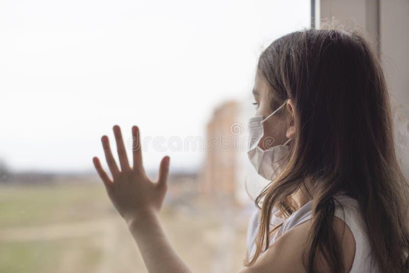 En liten flicka med mask för att skydda Covid-19 står nära fönstret och är ledsen Flickan blev sjuk och kan inte gå ut Wuhan royaltyfria bilder