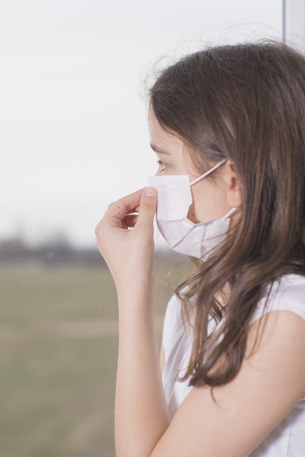 En liten flicka med mask för att skydda Covid-19 står nära fönstret och är ledsen Flickan blev sjuk och kan inte gå ut Wuhan royaltyfri foto