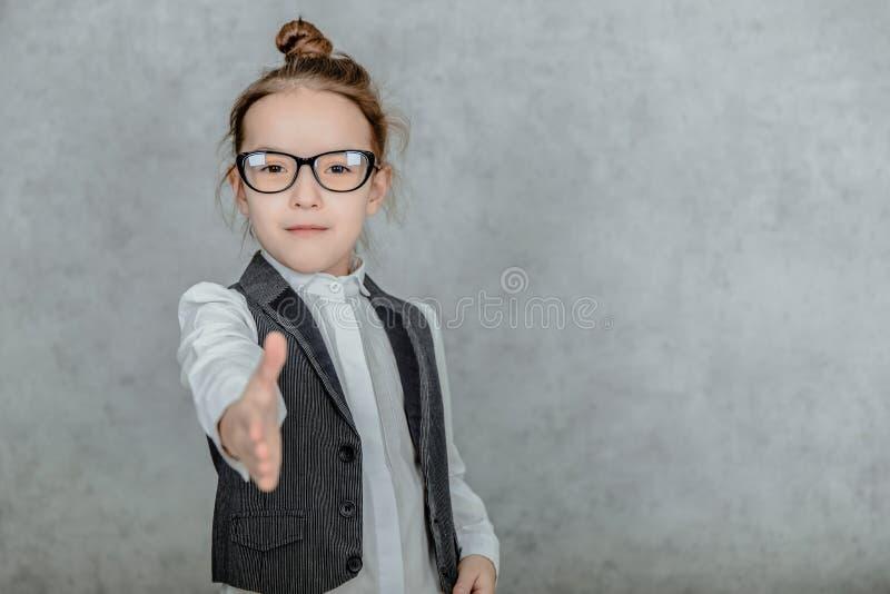En liten flicka på grå bakgrund Förklädd som en affärskvinna med svarta glasögon Isolerade på vit bakgrund arkivbilder