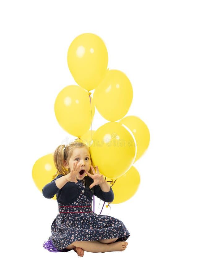 En liten flicka som sitter med ballonger, ett lekfullt och överraskat uttryck royaltyfria foton
