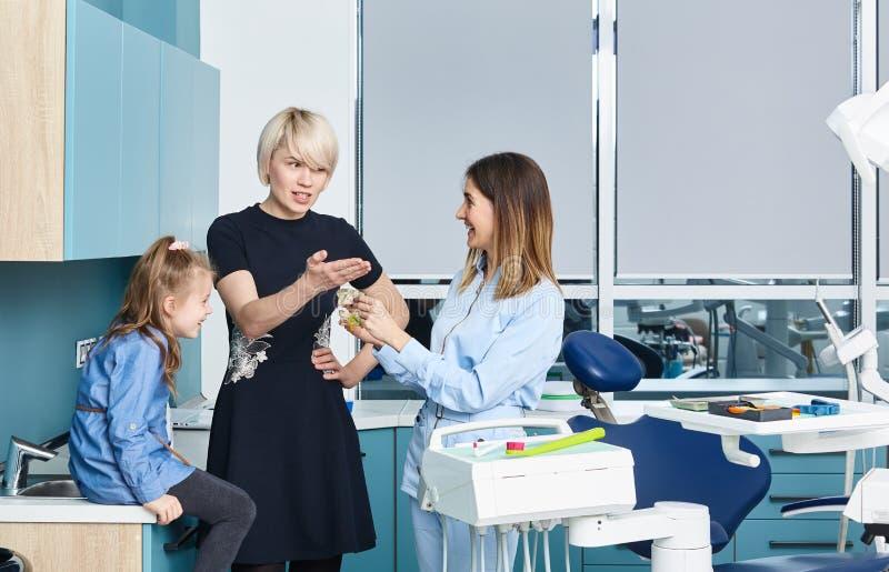 En liten flicka som tittar på medialt i munnen och spelar en läkare med en kvinnlig pediatrisk tandläkare i skåpet tandläkare arkivfoto