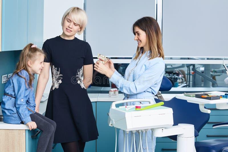 En liten flicka som tittar på medialt i munnen och spelar en läkare med en kvinnlig pediatrisk tandläkare i skåpet tandläkare arkivfoton