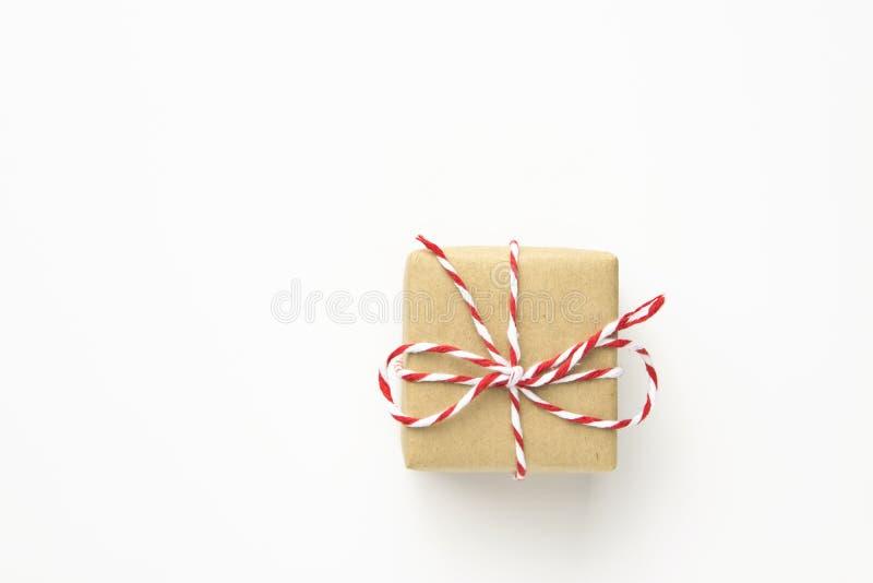 En liten gåvaask som slås in i brunt hantverkpapper som binds med det randiga röda bandet på vit bakgrund Presents för nytt år fö arkivfoton