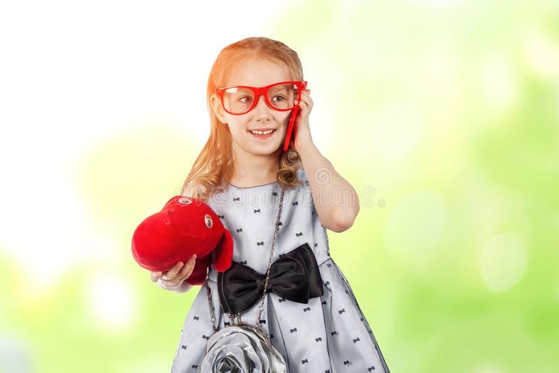 En liten glamorös flicka med röda exponeringsglas och en hund som talar på royaltyfri bild