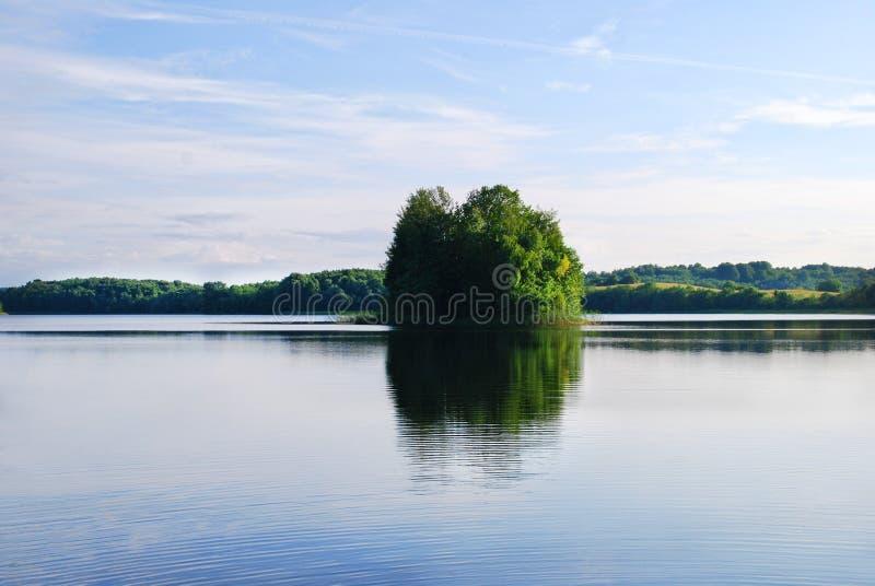 En liten grön ö som reflekterar i en blå sjö royaltyfri fotografi