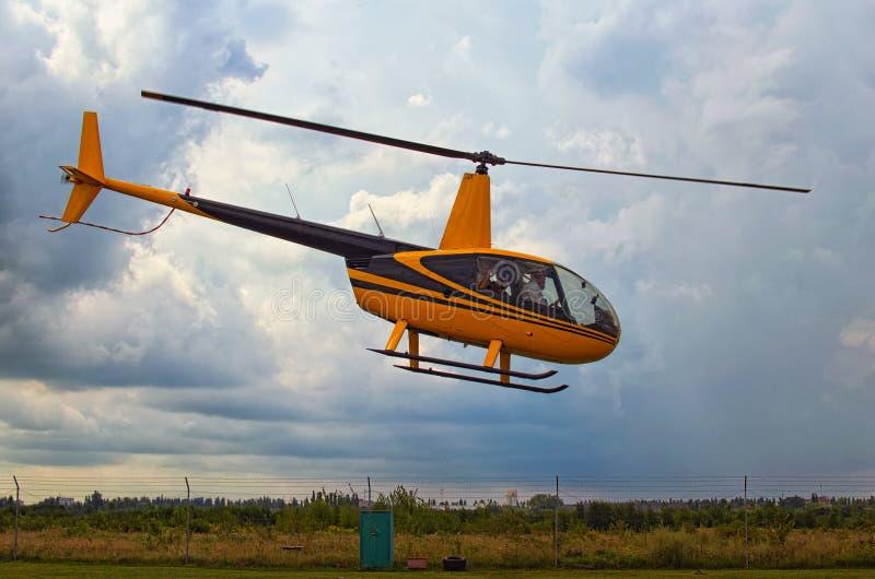 En liten gul helikopter tar av Stormmoln i bakgrunden Ett litet privat flygfält i Zhytomyr, Ukraina royaltyfria bilder