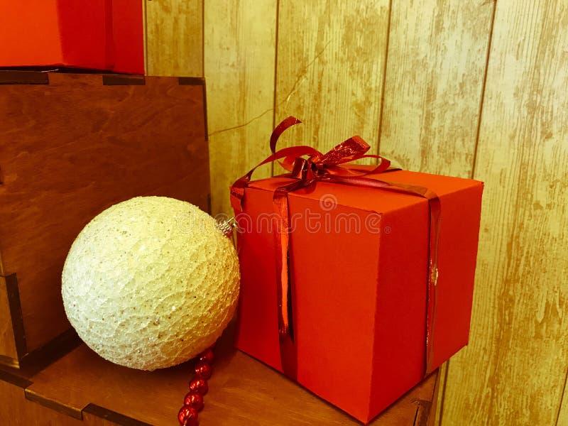 En liten gullig vit julgrangarnering, en boll och nytt års festliga garnering och en röd gåvaask fotografering för bildbyråer
