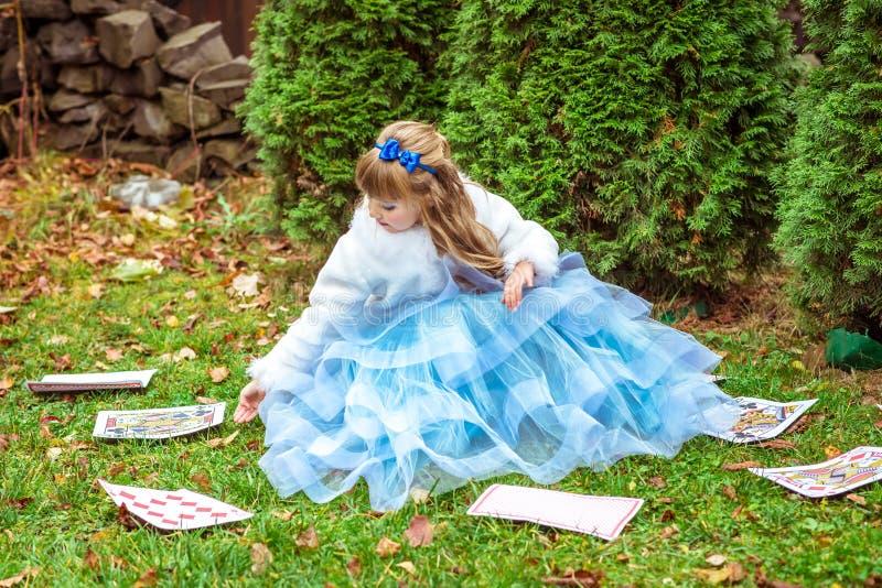 En liten härlig flicka i en lång blått klär sammanträde på gräset och att spela med stora modiga kort royaltyfri fotografi