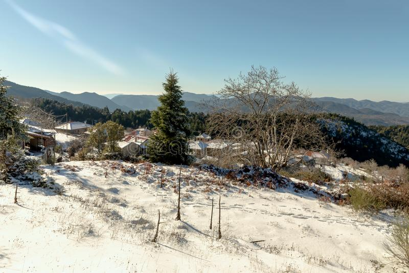 En liten by i bergen i vinter arkivfoto