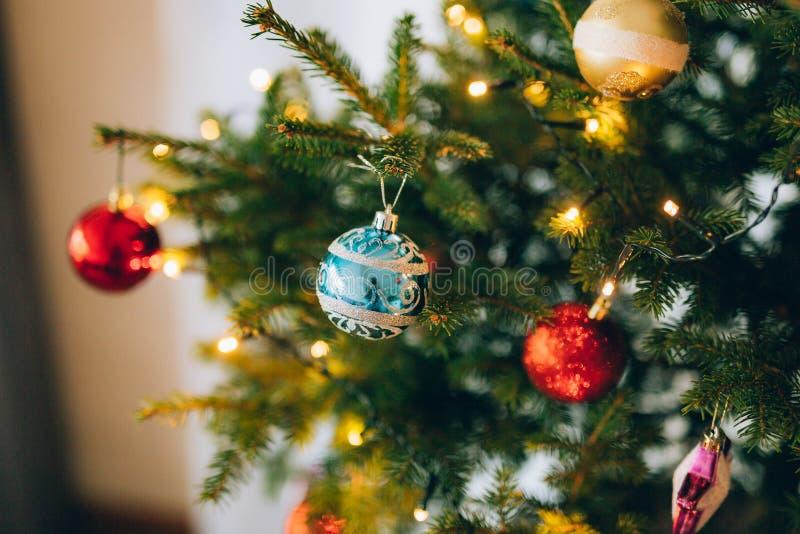 En liten julgran i en kruka som dekoreras med bollar, girlander royaltyfria bilder