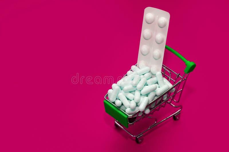 En liten karta fylld med läkemedel, en full korg med tabletter mot rosa bakgrund, medicinskt koncept royaltyfria bilder