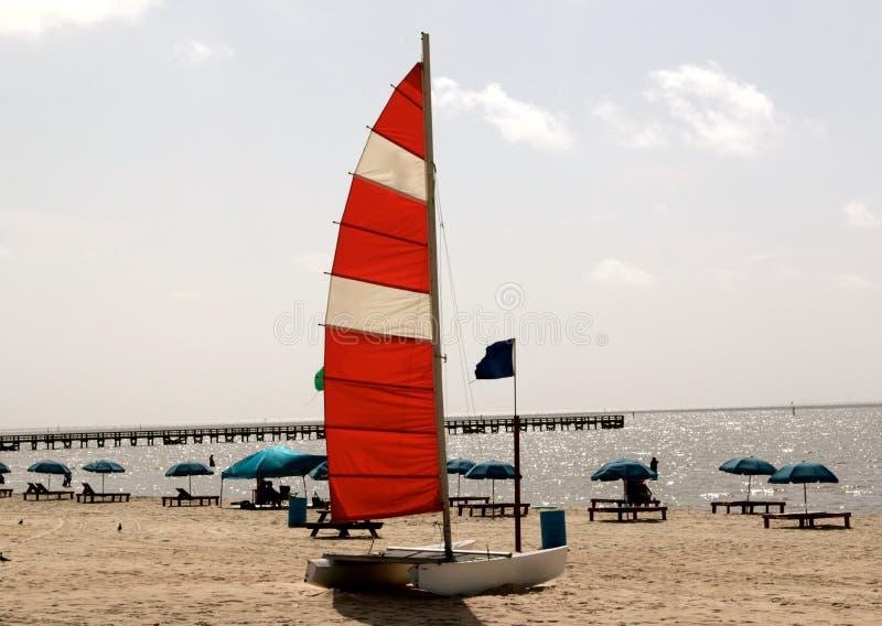 En liten katamaran med en segla förtöjde på en avskild strand royaltyfria bilder