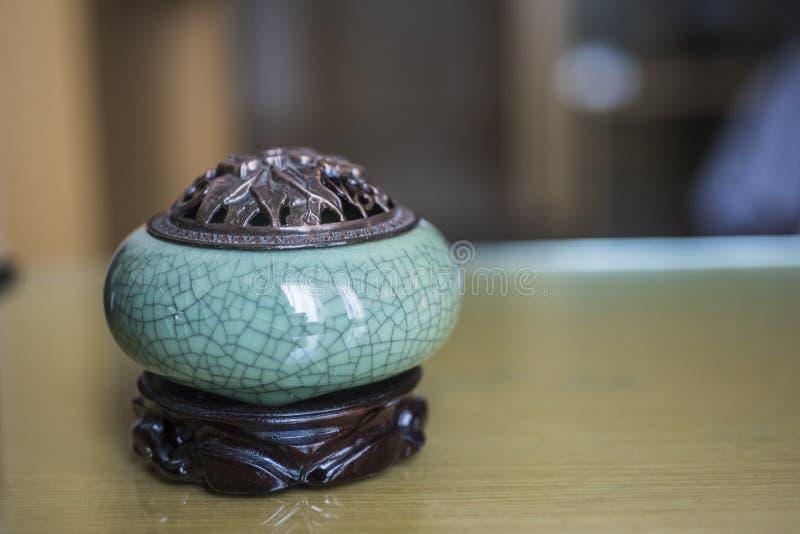 En liten keramisk rökelsekar på skrivbordet royaltyfri fotografi
