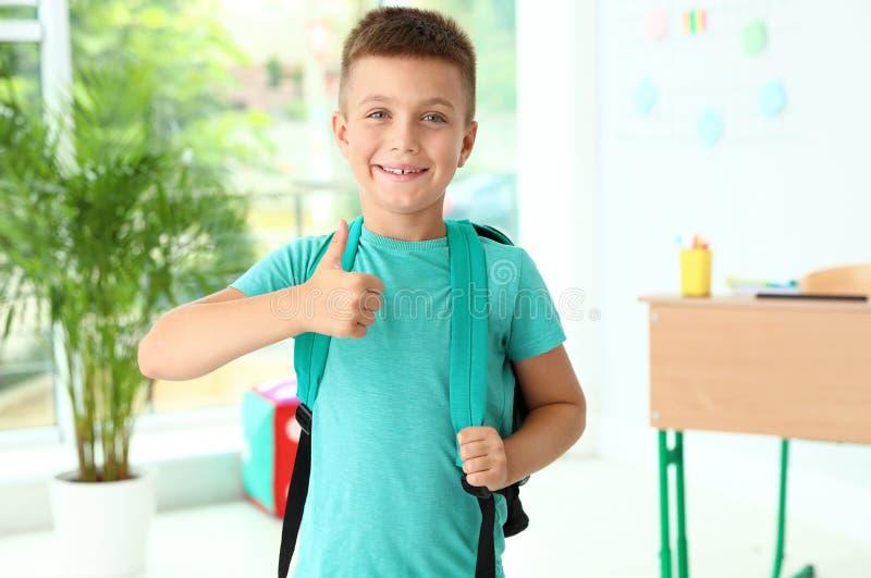 En liten kille med ryggsäck som visar upp tummarna i klassrum fotografering för bildbyråer