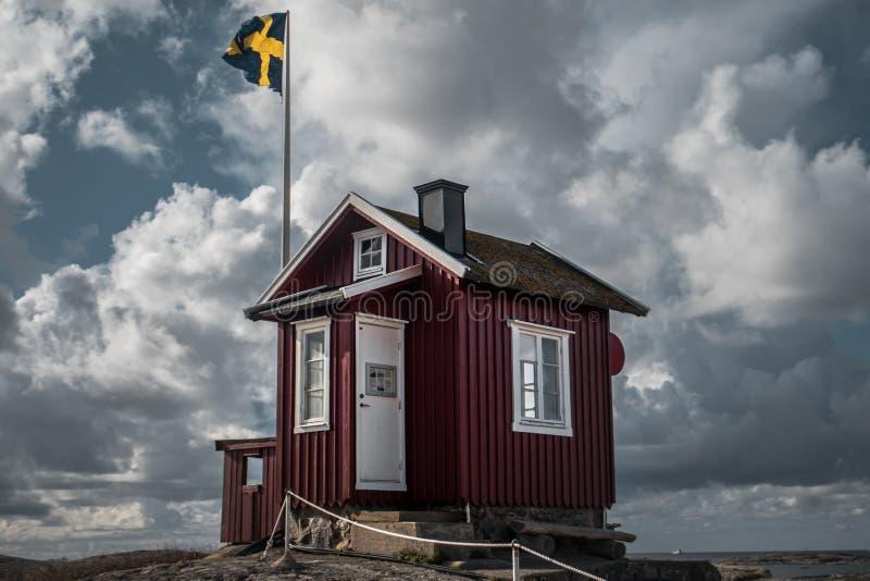 En liten koja framme av en svensk flagga royaltyfria bilder