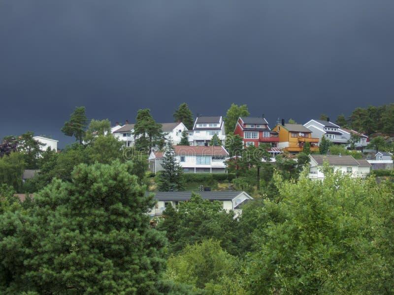 En liten modern by i berget omgiven av en tätt blandad skog i bakgrunden av moln före regnet Familj och arkivfoton