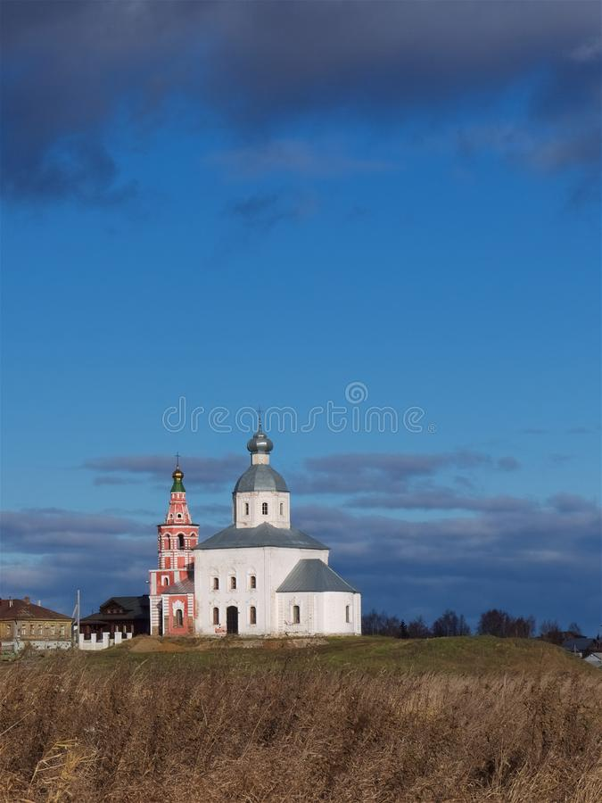 En liten ortodox kyrka på en kulle mot en blå himmel royaltyfri bild