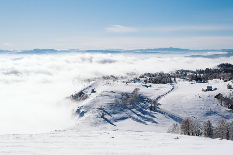 En liten by på överkanten av ett snöig berg i molnen royaltyfri fotografi