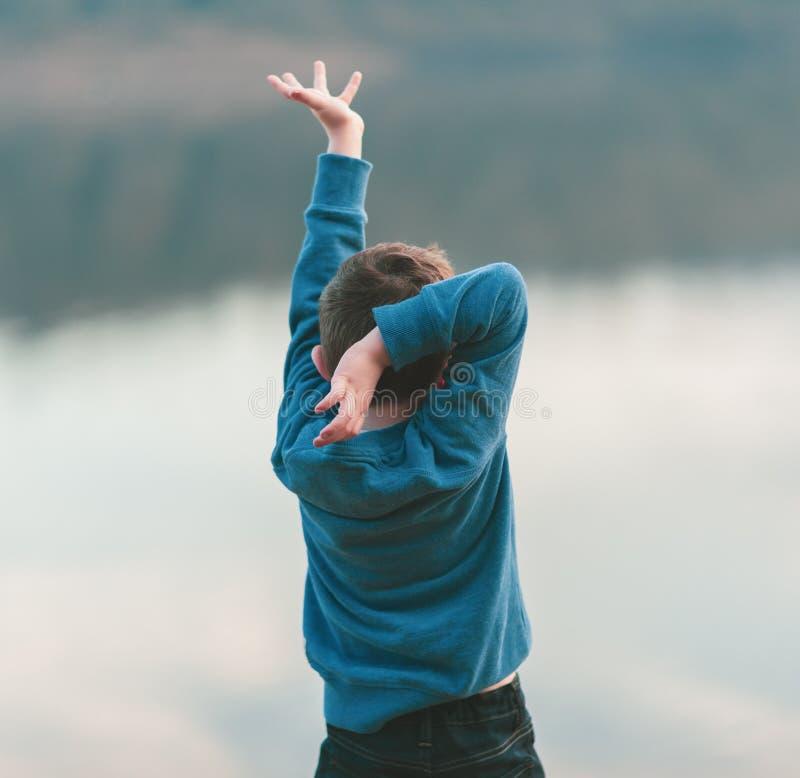 En liten pojke dansar mot en flodbakgrund royaltyfri bild
