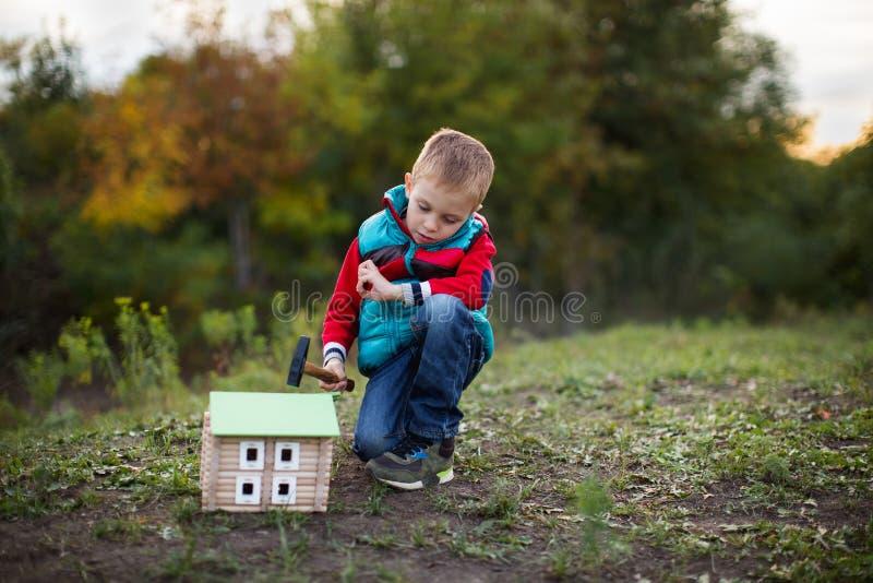 En liten pojke i en höstskog samlar en trähusformgivare royaltyfria foton