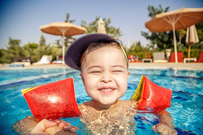 En liten pojke lär sig att simma i poolen på sommaren med stöd av sin fars händer royaltyfria foton
