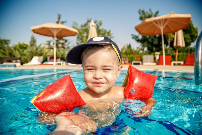 En liten pojke lär sig att simma i poolen på sommaren med stöd av sin fars händer arkivfoto