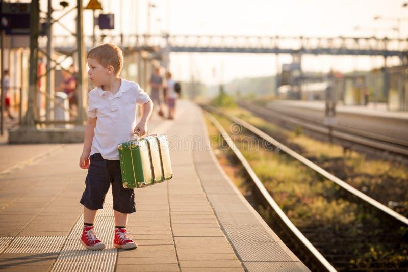 En liten pojke som är klädd i shorts och en polo t-shirt på en järnvägsstation och väntar på tåget royaltyfri fotografi