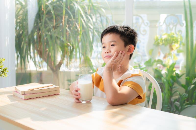 En liten pojke som dricker mjölk när han sitter på skrivbordet efter att ha gjort läxor Begreppet e-lärande och utbildning fotografering för bildbyråer