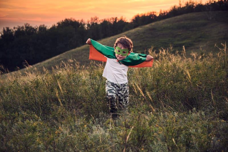 En liten pojke som spelar en superhjälte Kid i en superhjälte-kostym Ett lyckligt barn går och träffar fotografen royaltyfria foton