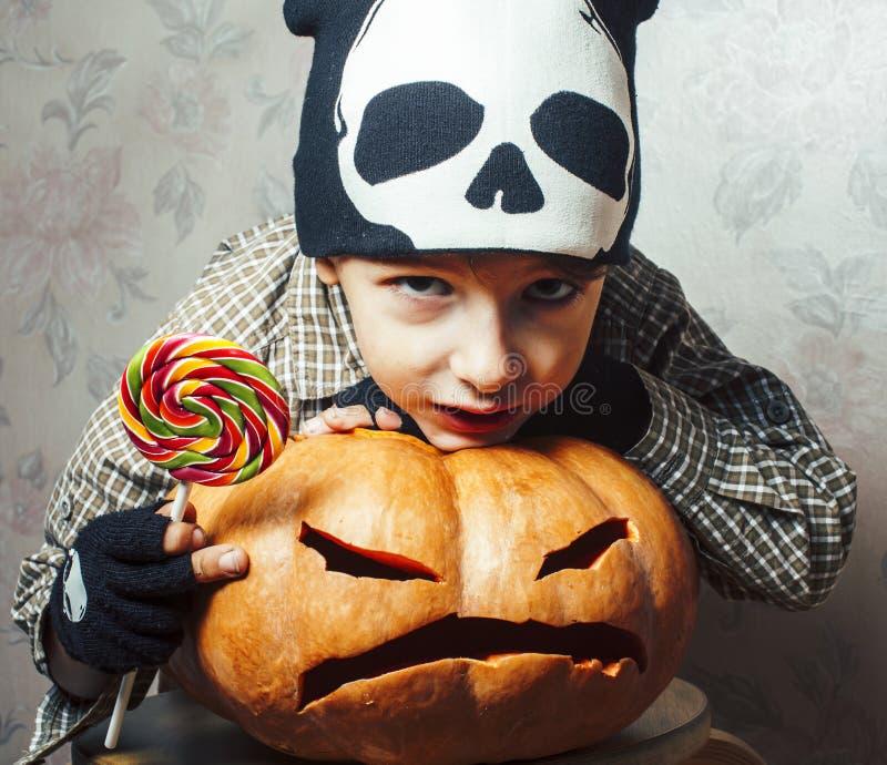 En liten, söt pojke i skeletthatt med pumpa och godis på halloween festdag, livsstilskoncept arkivfoton