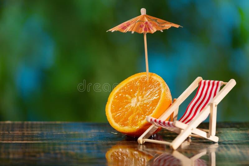 En liten schäslong och halva en apelsin med ett coctailparaply på våta bräden, mot bakgrunden av grönska, begreppet arkivfoto