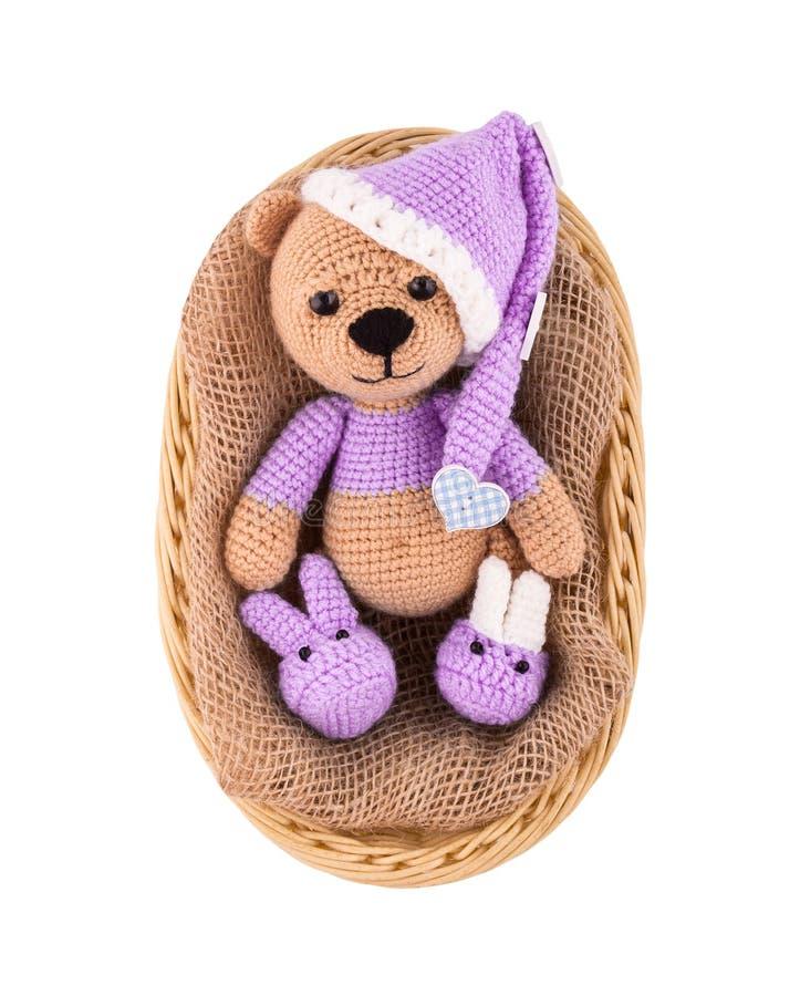 En liten stucken nallebjörn i en vide- korg En sömnig björngröngöling i en hatt och byten Amigurumi handgjort Isolerat på vit royaltyfria foton