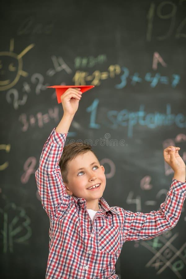 En liten student lanserar ett rött flygplan i klassrumet mot bakgrunden av ett bräde royaltyfri bild