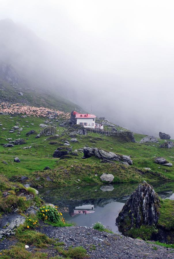 en liten stuga under den höga klippan av bergen arkivbilder