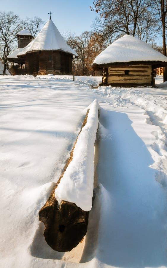 En liten träkyrka och stuga som täckas i snö på bymuseet, Bucharest arkivfoto