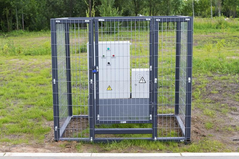 En liten transformator bak ett metallraster fotografering för bildbyråer