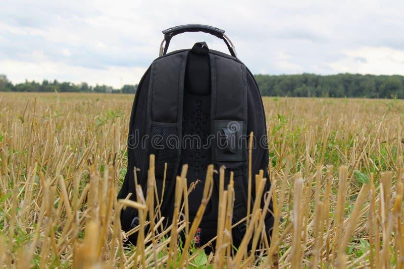 En liten turist- ryggsäck står på jordningen i mitt av ett slutta fält arkivbild