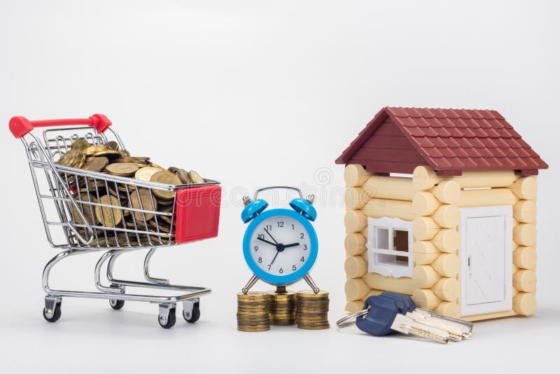 En livsmedelsbutikvagn som fylls med mynt, en skrivbordklocka, en grupp av tangenter och en lekstuga arkivfoton