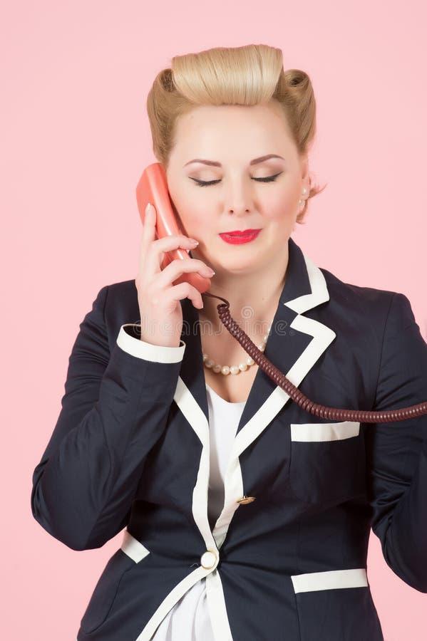 En livsstil och ett folkbegrepp: den blonda kvinnan talar på den röda telefonmottagaren över rosa bakgrund, stängd ögonkonversati fotografering för bildbyråer