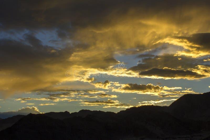 En ljus färgrik solnedgånghimmel mot bakgrunden av en kontur av ett berg royaltyfria bilder