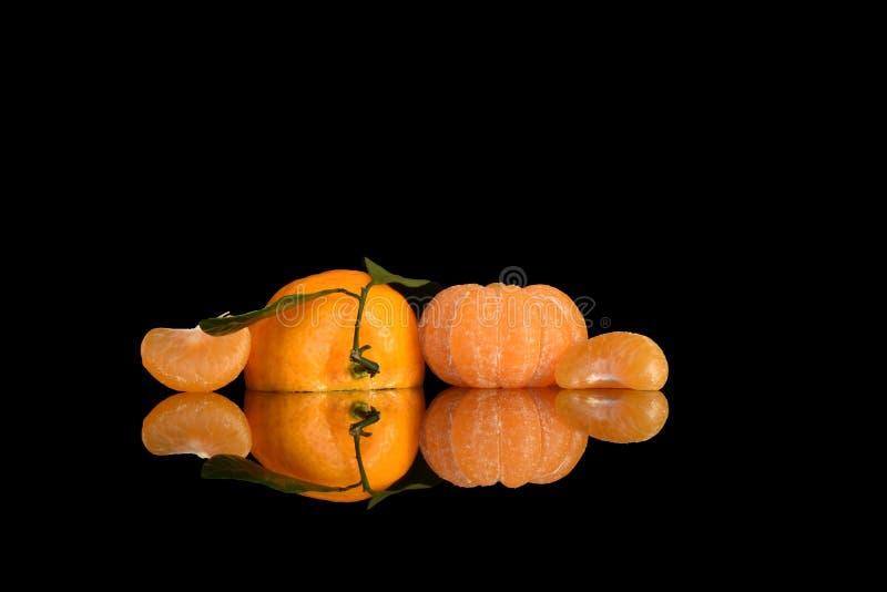 En ljus sammansättning av tangerin på en svart backgroundер royaltyfri foto