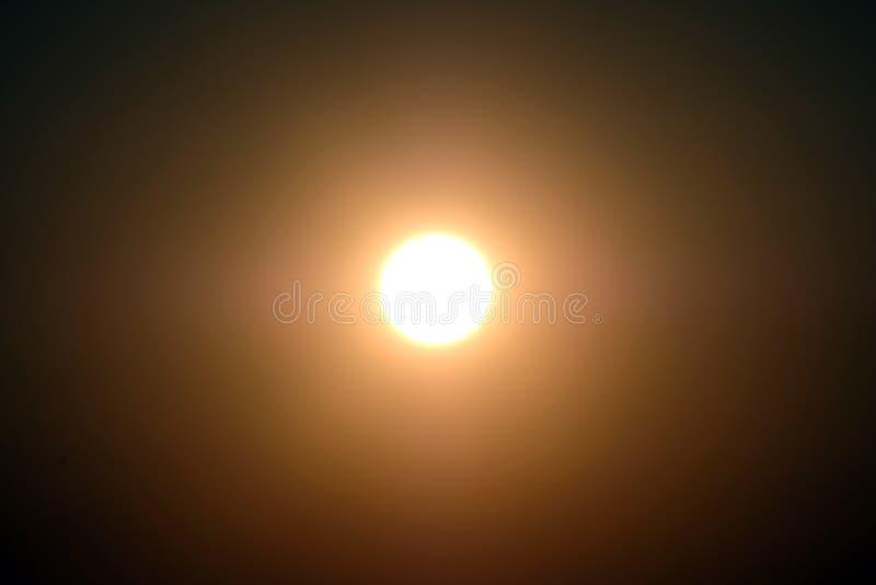 En ljus sol eller måne i mitten på en mörk himmel Märkes- bakgrund royaltyfria bilder