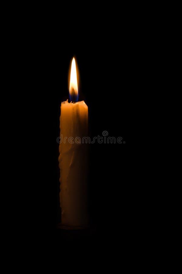 En ljus stearinljus som ljust bränner i den svarta bakgrunden royaltyfria bilder