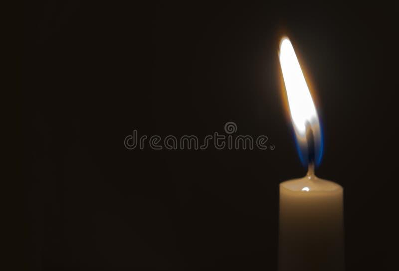 En ljus stearinljus som ljust bränner i den svarta bakgrunden arkivfoton