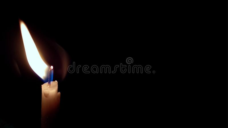 En ljus stearinljus som ljust br?nner i den svarta bakgrunden royaltyfri bild