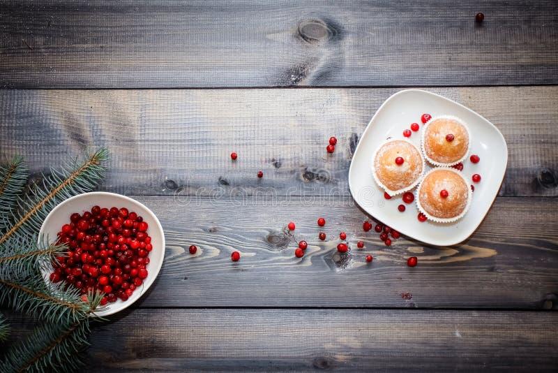 En ljus trätabellöverkant med en platta av nytt bakade muffin som dekoreras med röda bär som strilas med vitt pulver och en platt arkivfoton