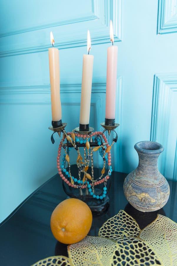 En ljusstake med en tillbringare är på tabellen royaltyfria foton