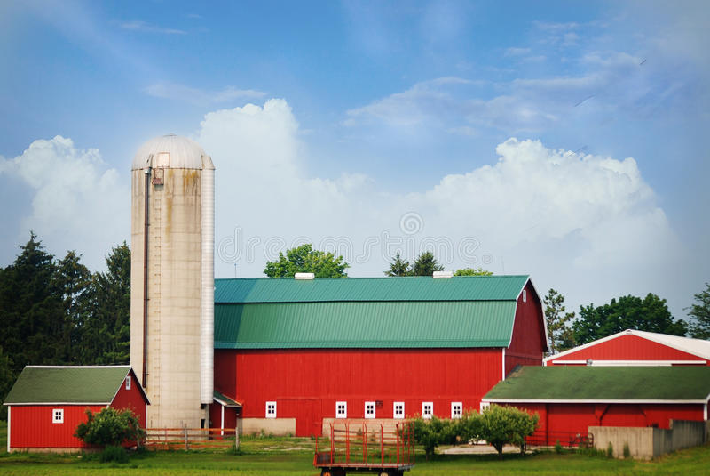 En ljust röd kulör ladugård med ett grönt tak på en sommardag royaltyfria bilder