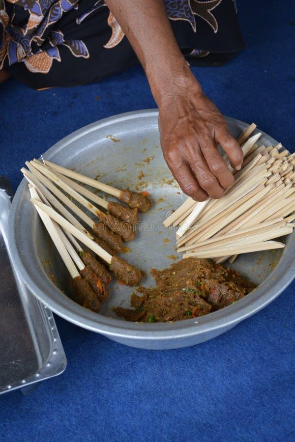 En lokal fläder förbereder en kulturell maträtt som kallas satay lilit arkivfoto