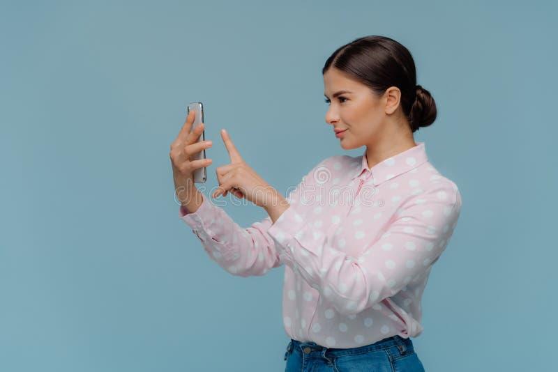 En longueur tiré de la dame de brune a peigné des cheveux, tient le téléphone portable moderne, fait le portrait de selfie, utili photographie stock